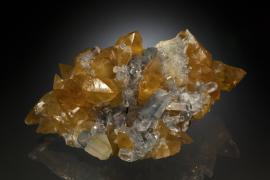 Celestine and calcite, Maybee, Monroe County, Michigan. Maybee produced some of the finest celestine specimens ever found in North America. This specimen is a particularly rare combination of celestine with golden calcite. Specimen 17 cm wide. Photo by J. Jaszczak and C. Stefano. (DM 25331)