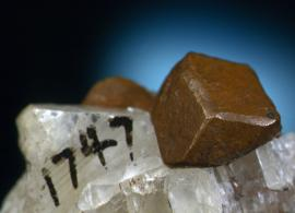 Copper, Franklin Mine, Houghton County, Michigan. A sharp dodecahedral crystal of copper on calcite. From the collection of J. T. Reeder. Field of view is about 4 cm wide. Photo by J. Jaszczak. (JTR 1747)