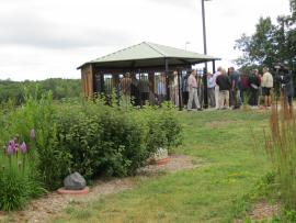 A crowd of people examine the native copper slab during dedication of the Copper Pavilion August 2015