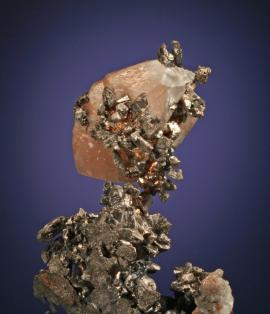 Calcite, silver and copper, South Hecla Mine, Houghton County, Michigan. A unique specimen of copper-included calcite perched on silver crystals. Donor: W. Weir. Specimen 7 cm tall. Photo by G. Robinson. (DM 168)