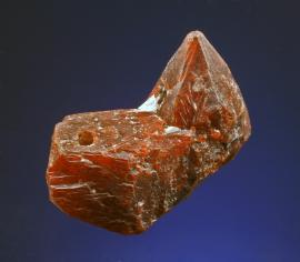 Zincite, Franklin, New Jersey. An outstanding crystal of zincite from Franklin. It was acquired from the family of a Keweenaw copper miner who had used it for years as a watch fob (the hole drilled to accommodate this usage is visible on the left side of the specimen in the photo).  Specimen 3 cm wide.Photo by G. Robinson. (DM 30818)